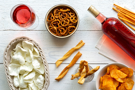 Rose wine with savoury party snacks on rustic white wood background from above. Standard-Bild