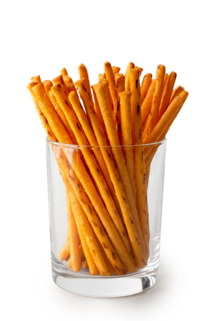 Crunchy thin cheese sticks in glass isolated on white. Stock Photo