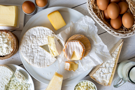 Cheese, milk, dairy products and eggs on rustic white wood from above.