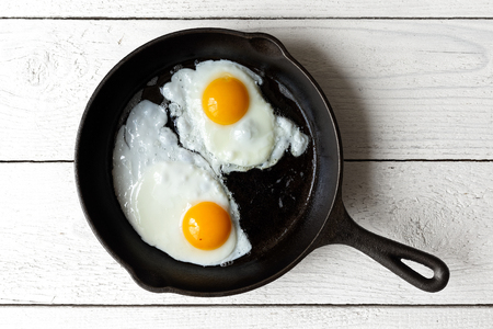 Two fried eggs in cast iron frying pan isolated on white painted wood from above. Фото со стока