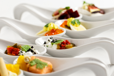 A row of mixed canapes in white ceramic spoons on white background.