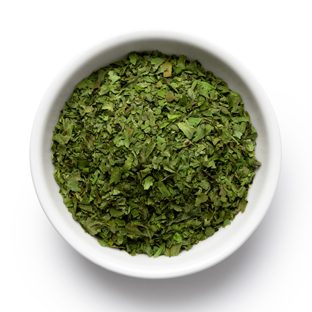 Dried chopped coriander leaves in white ceramic bowl isolated on white from above.