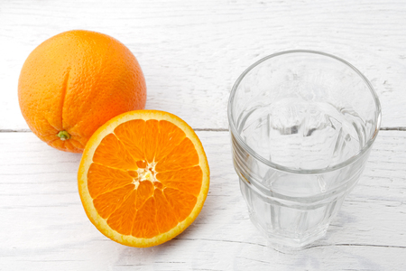 One whole and cut half of orange next to an empty glass isolated on white painted wood. Imagens