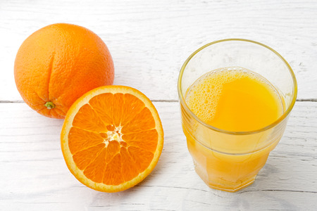 One whole and half of orange next to a glass of fresh orange juice isolated on white painted wood.