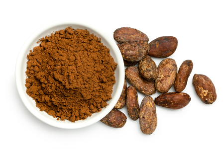 Cocoa powder in a white ceramic bowl next to roasted unpeeled cocoa beans isolated on white from above. Imagens