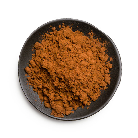 Cocoa powder in a black ceramic dish isolated on white from above.