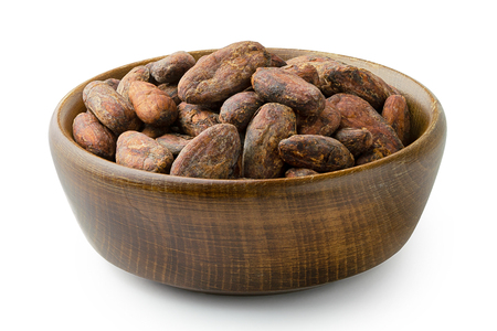 Roasted unpeeled cocoa beans in a brown wooden bowl isolated on white. Imagens