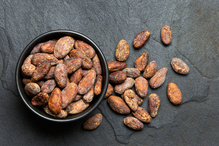Roasted unpeeled cocoa beans in a black ceramic bowl next to unpeeled cocoa beans isolated on black slate from above.