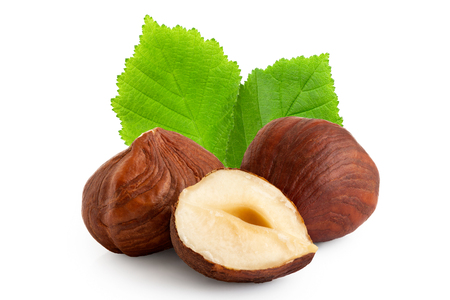 Two and half hazelnuts with skin and green leaves isolated on white. Closeup.