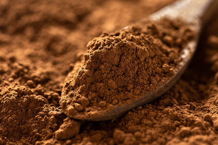 Detail of cocoa powder on a wooden spoon sitting on cocoa powder. Blurred background.