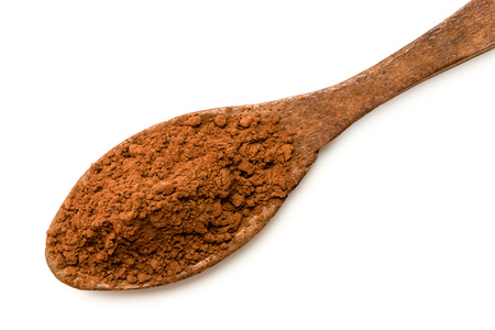Cocoa powder on a wooden spoon isolated on white from above.