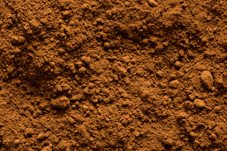 Background of ground cocoa powder from above.