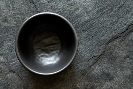 Black empty ceramic bowl isolated on dark grey slate from above. Space for text.