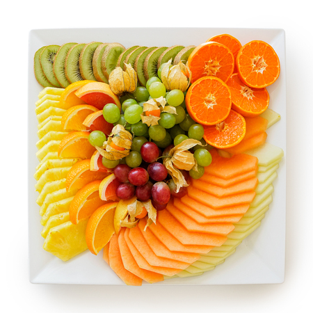 Mix of freshly cut tropical and citrus fruit arranged on white square ceramic platter isolated on white from above.