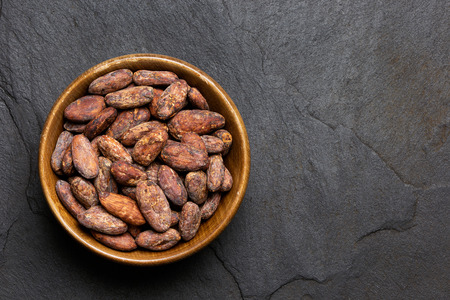 Roasted unpeeled cocoa beans in a brown wooden bowl isolated on black slate from above. Space for text. Imagens