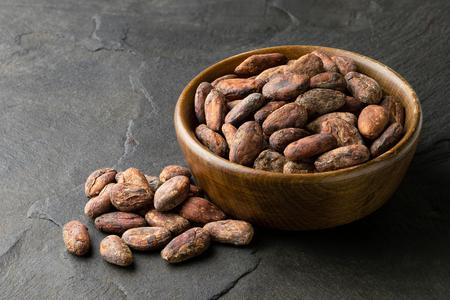 Geröstete ungeschälte Kakaobohnen in einer braunen Holzschale neben einem Stapel ungeschälter Kakaobohnen einzeln auf schwarzem Schiefer.