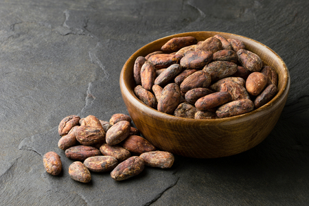 Roasted unpeeled cocoa beans in a brown wooden bowl next to a pile of unpeeled cocoa beans isolated on black slate.