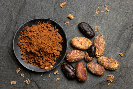 Cocoa powder in a black ceramic dish next to roasted peeled and unpeeled cocoa beans and chocolate shavings on black slate from above.