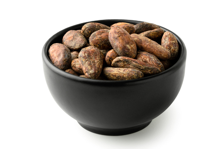 Roasted unpeeled cocoa beans in a black ceramic bowl isolated on white.
