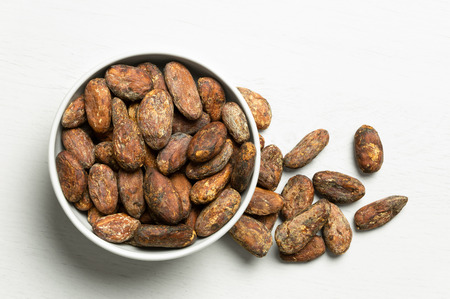 Roasted unpeeled cocoa beans in a white ceramic bowl next to a pile of unpeeled cocoa beans isolated on white painted wood  from above.