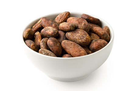 Roasted unpeeled cocoa beans in a white ceramic bowl isolated on white.