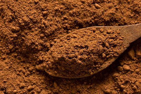 Detail of cocoa powder on a wooden spoon sitting on cocoa powder from above. Imagens