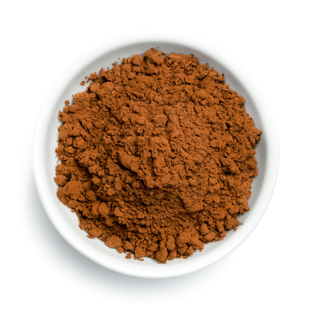 Cocoa powder in a white ceramic bowl isolated on white from above.