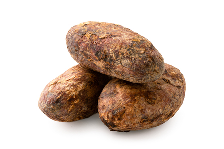 Pile of three roasted unpeeled cocoa beans isolated on white.