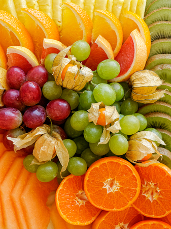 Background of arranged freshly cut tropical and citrus fruit from above. Closeup.