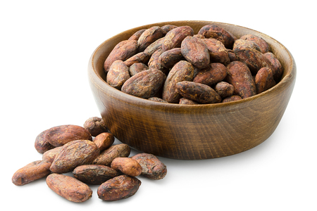 Unpeeled cocoa beans in a brown wooden bowl next to a pile of unpeeled cocoa beans isolated on white.