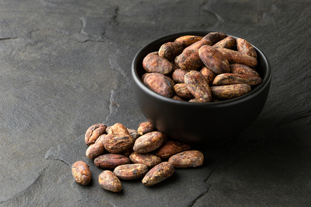 Roasted unpeeled cocoa beans in a black ceramic bowl next to a pile of unpeeled cocoa beans isolated on black slate.