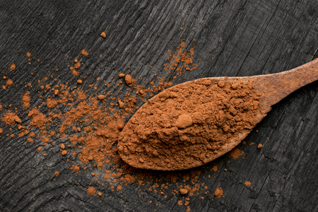 Cocoa powder on a wooden spoon isolated on black rustic wood board from above. Spilt cocoa. Space for text.