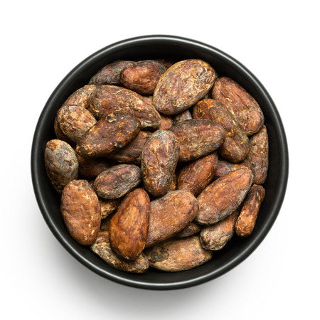 Roasted unpeeled cocoa beans in a black ceramic bowl isolated on white from above. Imagens