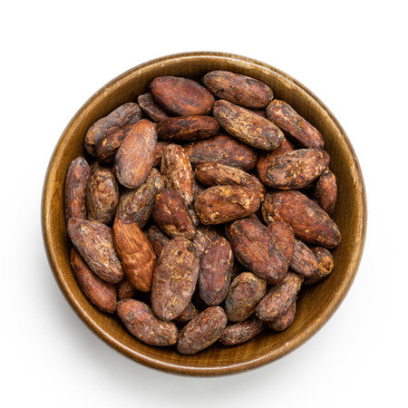 Roasted unpeeled cocoa beans in a brown wooden bowl isolated on white from above. Imagens