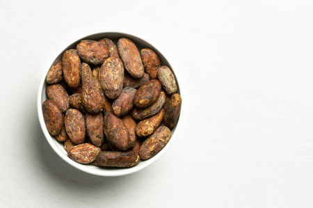 Roasted unpeeled cocoa beans in a white ceramic bowl isolated on white painted wood from above. Space for text. Imagens