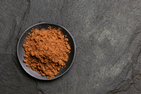 Cocoa powder in a black ceramic dish isolated on black slate from above. Space for text.