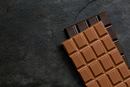 A slab of milk chocolate on top of a slab of dark chocolate on black slate from above. Space for text.
