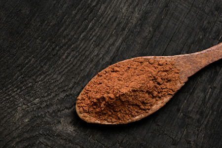 Cocoa powder on a wooden spoon isolated on black rustic wood board from above. Space for text.