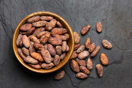 Roasted unpeeled cocoa beans in a brown wooden bowl next to unpeeled cocoa beansl isolated on black slate from above. Imagens
