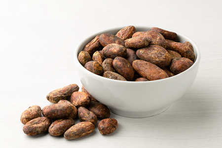 Roasted unpeeled cocoa beans in a white ceramic bowl next to a pile of unpeeled cocoa beans isolated on white painted wood.