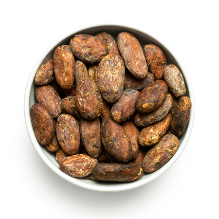 Roasted unpeeled cocoa beans in a white ceramic bowl isolated on white from above.