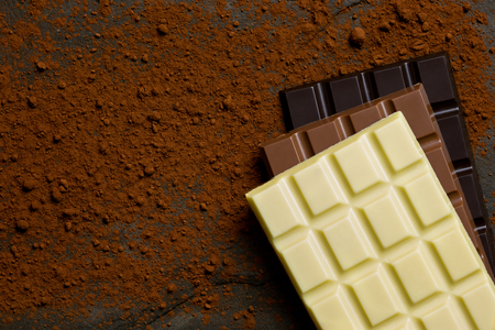 Slabs of white, milk and dark chocolate on top of each other on a black slate dusted with cocoa powder from above. Space for text.