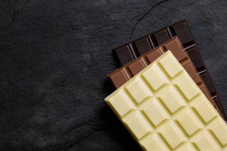 Slabs of white, milk and dark chocolate on top of each other on a black slate from above. Space for text. Imagens