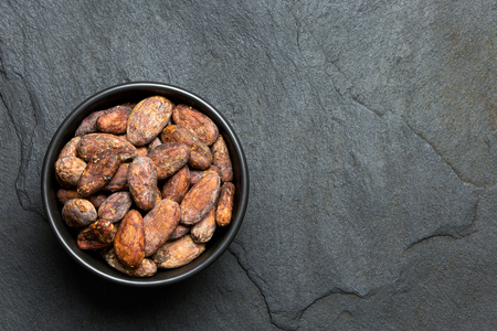 Roasted unpeeled cocoa beans in a black ceramic bowl isolated on black slate from above. Space for text.