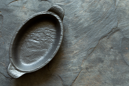 Black empty ceramic dish isolated on grey slate from above. Space for text.