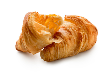 One and half baked plain croissants isolated on white.
