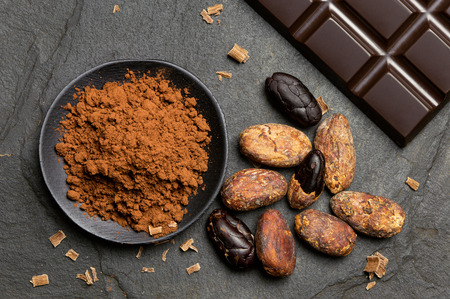 Cocoa powder in a black ceramic dish next to roasted peeled and unpeeled cocoa beans, chocolate shavings and a slab of dark chocolate on black slate from above.