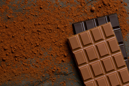 A slab of milk chocolate on top of a slab of dark chocolate on black slate dusted with cocoa powder from above. Space for text.