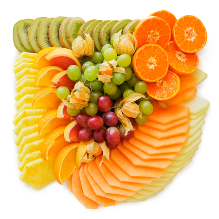 Mix of arranged freshly cut tropical and citrus fruit isolated on white from above.