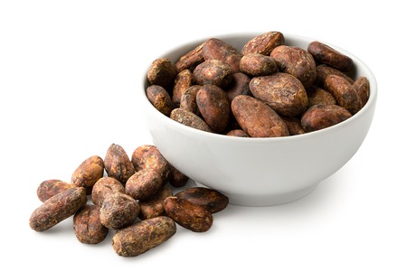 Roasted unpeeled cocoa beans in a white ceramic bowl next to a pile of unpeeled cocoa beans isolated on white.